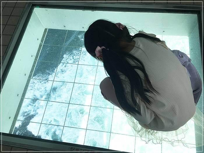 「渦の道」の展望台のガラス床を見る娘